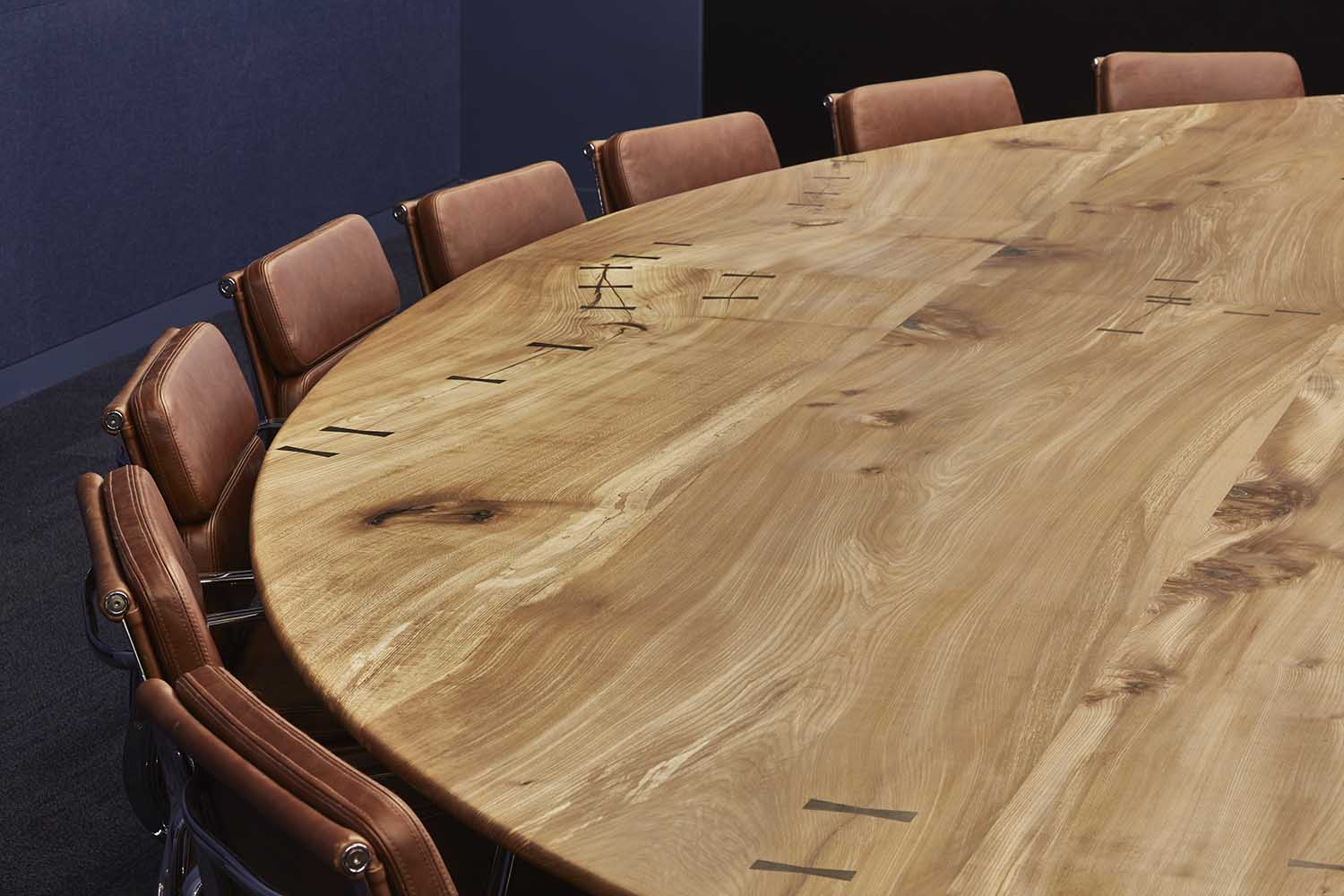 Bespoke eliptical boardroom table made from solid elm with bog oak butterfly ties