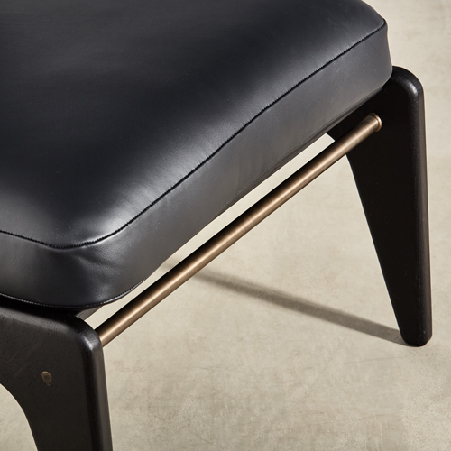 brass detailing on ebonised chair with leather upholstery